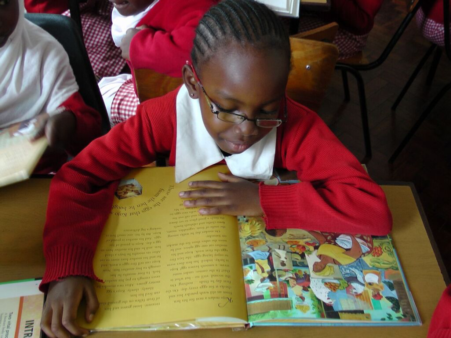 A girl reading a picture book.